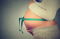 Cropped image pregnant woman with measuring tape around her belly Royalty Free Stock Photos