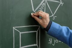 Cropped image of professor drawing with piece of chalk. At blackboard royalty free stock photos