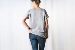 Cropped image. Rear view of young woman, dressed in a gray T-shirt and blue jeans, standing for light background Royalty Free Stock Photography