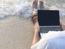 Cropped image of relaxed man in casual clothes using laptop on the beach with wave of sea.  Stock Images