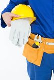 Cropped image of repairman holding helmet and gloves Stock Image