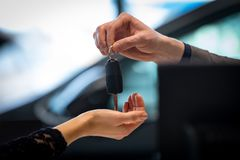Cropped image of salesman giving car key to customer. In showroom Stock Photos