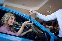 Cropped image of salesman giving keys to customer Stock Image