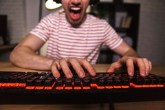 Cropped image of Screaming gamer playing video games on computer. While sitting by the table at home stock image