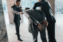 Cropped image of security guards arresting offender and talking. By portable radio royalty free stock photos