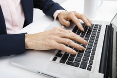 Cropped image of senior businesswoman typing on laptop Royalty Free Stock Image