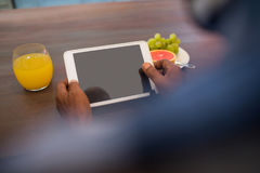 Cropped image of senior man using tablet. While sitting at table Stock Photos