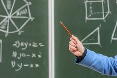 Cropped image of senior professor pointing on something with pencil. On blackboard stock image