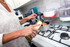 Cropped image of senior woman adding olive oil to saucepan at kitchen counter Stock Image