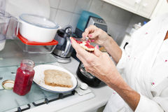 Cropped image of senior woman applying jam on toast in kitchen Stock Images