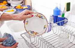 Cropped image of senior woman arranging plate in rack at kitchen counter Stock Photos