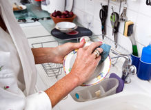 Cropped image of senior woman cleaning plate in kitchen Stock Photography