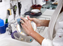 Cropped image of senior woman cleaning plate in kitchen Royalty Free Stock Images