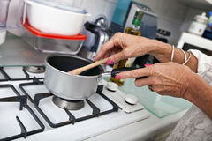 Cropped image of senior woman cooking at kitchen counter Stock Images