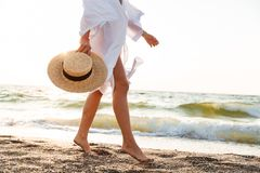 Cropped image of a slim young woman. In summer clothes holding hat, walking along the beach Stock Photos