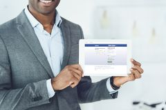 Cropped image of smiling african american man showing tablet with loaded facebook page royalty free stock image