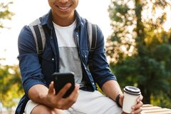 Cropped image of Smiling asian male student using smartphone stock photos