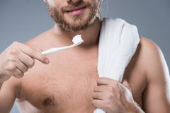 Cropped image of smiling bearded man with towel on shoulder holding toothbrush with toothpaste in hand,. Isolated on gray Royalty Free Stock Images
