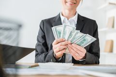 Cropped image of smiling financier counting money. In office stock photo