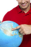 Cropped image smiling man pointing at the globe Stock Images