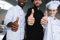 Cropped image of smiling multicultural chefs showing thumbs up. At restaurant kitchen royalty free stock photography