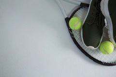 Cropped image of sports shoe with balls on racket Stock Photography