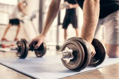 Cropped image of sportsman preparing doing push ups on dumbbells. In gym stock image