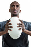 Cropped image of sportsman pressing rugby ball while looking up Royalty Free Stock Image