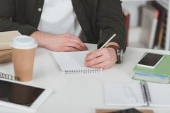 Cropped image of student making notes. In library Stock Photo