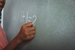 Cropped image of student writing on blackboard. In classroom Stock Image