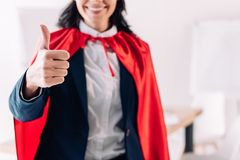 Cropped image of super businesswoman. In cape showing thumb up in office royalty free stock photography