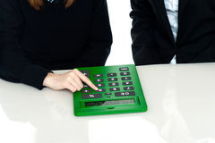 Cropped image of teacher and a student. Working out on a large green calculator Stock Photos