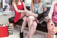 Cropped image of teen girls sitting on bench relaxing after shopping in clothing store. Young stylish woman tying up new. Cropped image of teen girls sitting on stock image