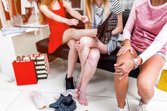 Cropped image of teen girls sitting on bench relaxing after shopping in clothing store. Young stylish woman tying up new. Cropped image of teen girls sitting on royalty free stock image