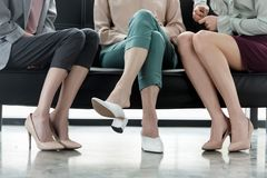 Cropped image of three businesswomen sitting on sofa. In office stock images