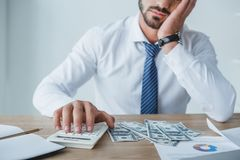 Cropped image of tired financier counting money with calculator. In office royalty free stock photo