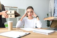 Tired woman with headache. Cropped image of tired woman with headache having a lot of work Stock Photography