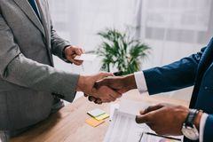 Cropped image of two businessmen shaking hands and giving visit cards to each other royalty free stock images