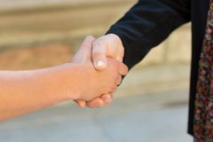 Cropped Image Of University Students Shaking Hands Stock Images