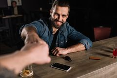 cropped image of visitor and bartender bumping fists royalty free stock photos