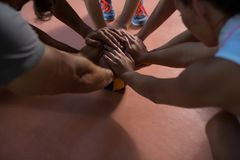Cropped image of volleyball players stacking hands. At court royalty free stock photography
