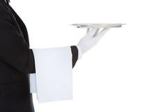 Cropped image of waiter holding empty tray