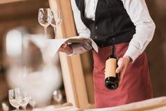 Waiter holding wineglasses and bottle Stock Image