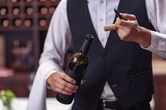 Cropped image waiter opening wine bottle. With corkscrew stock images