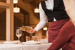 Waiter pouring wine into glass. Cropped image of Waiter pouring white wine into glass Stock Photos