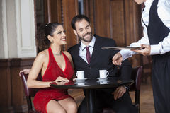 Cropped Image Of Waiter Serving Coffee To Couple Stock Photography