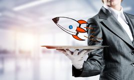 Hand of waiter presenting sketched rocket on tray. Cropped image of waitress`s hand in white glove presenting sketched flying missile on metal tray with office stock image