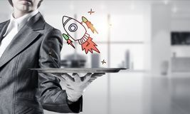 Hand of waiter presenting sketched rocket on tray. Cropped image of waitress`s hand in white glove presenting sketched flying missile on metal tray with office stock photo