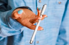 Woman in blue shirt Hold pen in your hand. pen spinning Stock Image