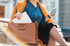 Cropped image of a woman in coat holding mobile phone Stock Photo